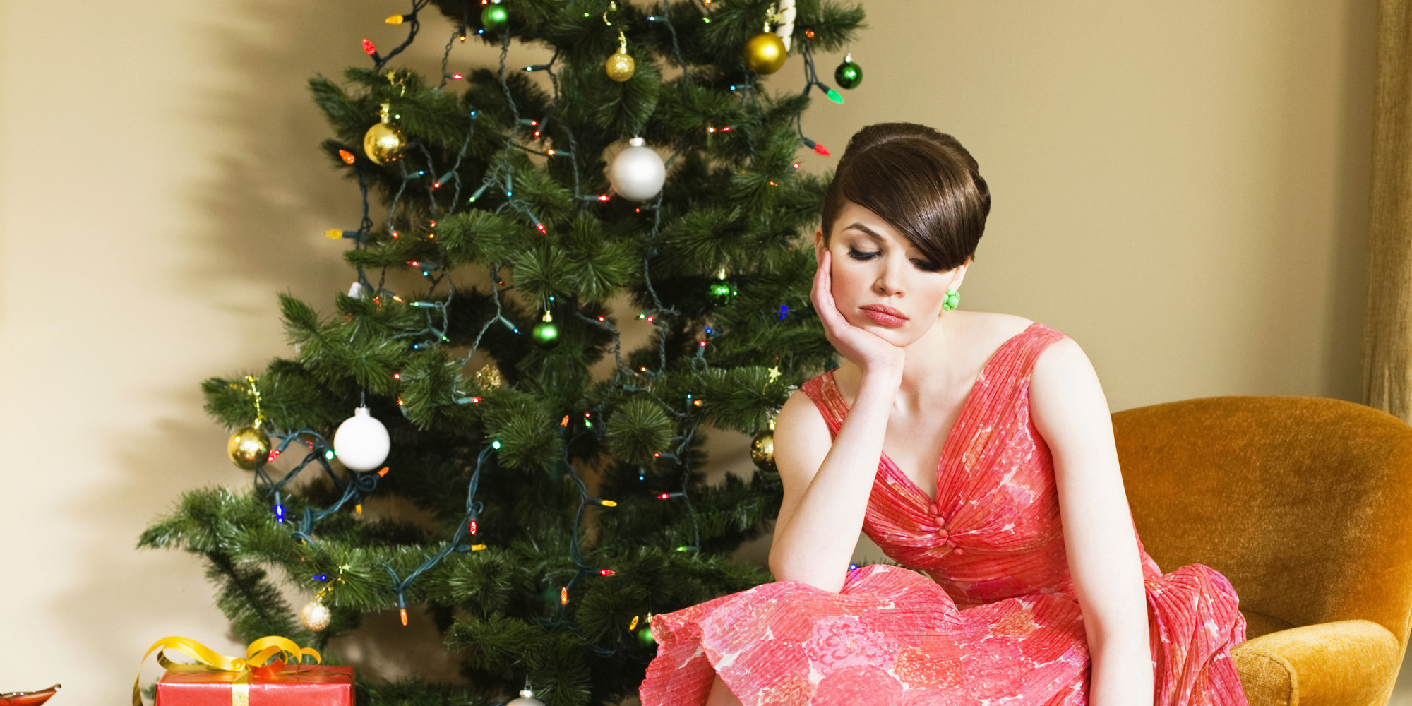 unhappy woman sitting next to christmas tree