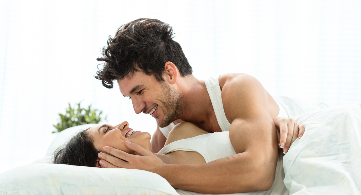 Happy young couple lying down in bed