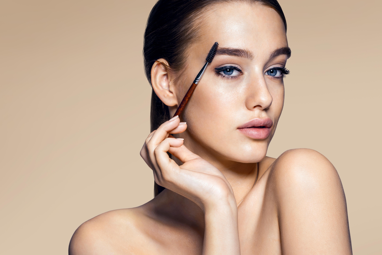 Beautiful woman using mascara