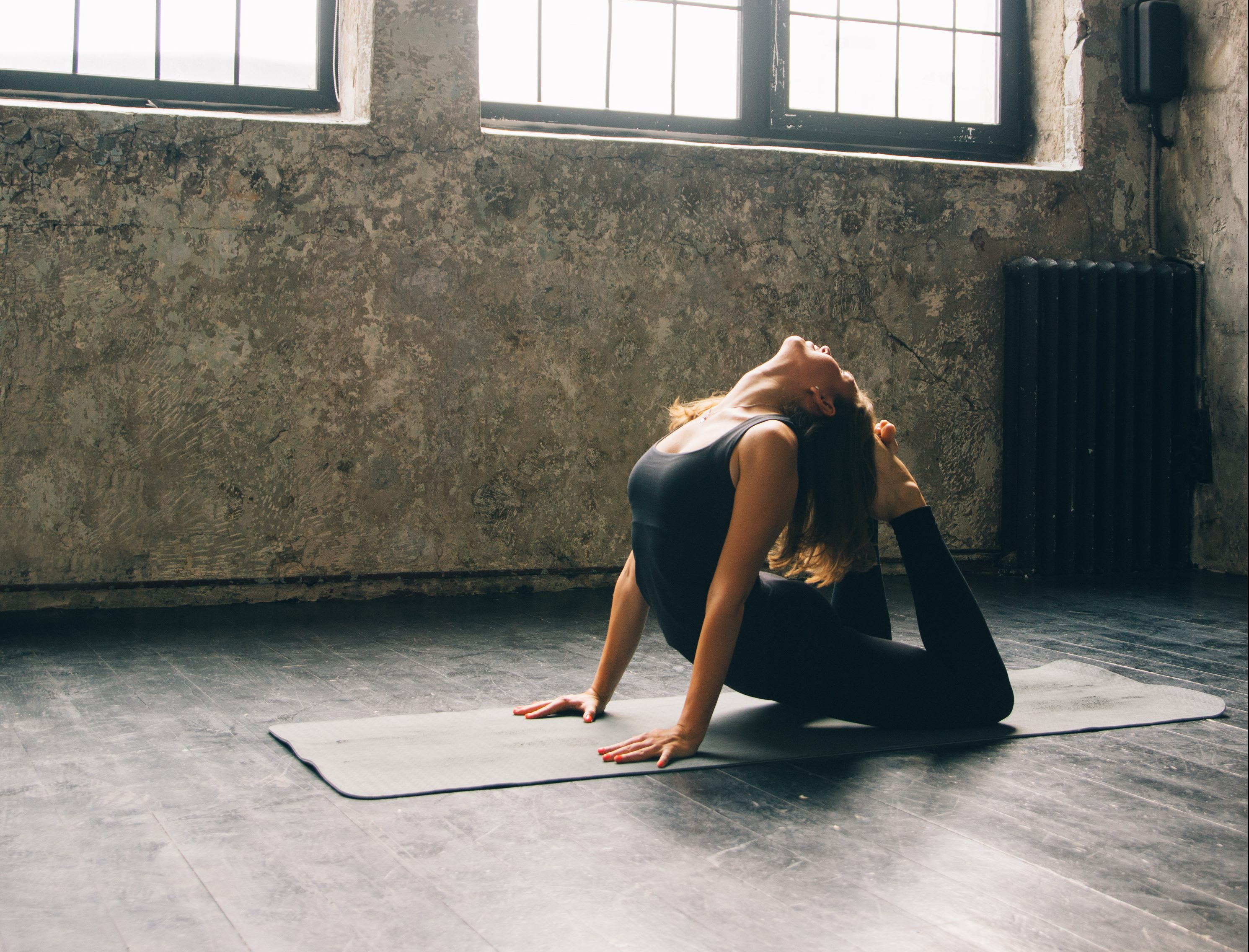 Young woman practicing yoga in urban loft: Cobra Pose (Bhujangasana)