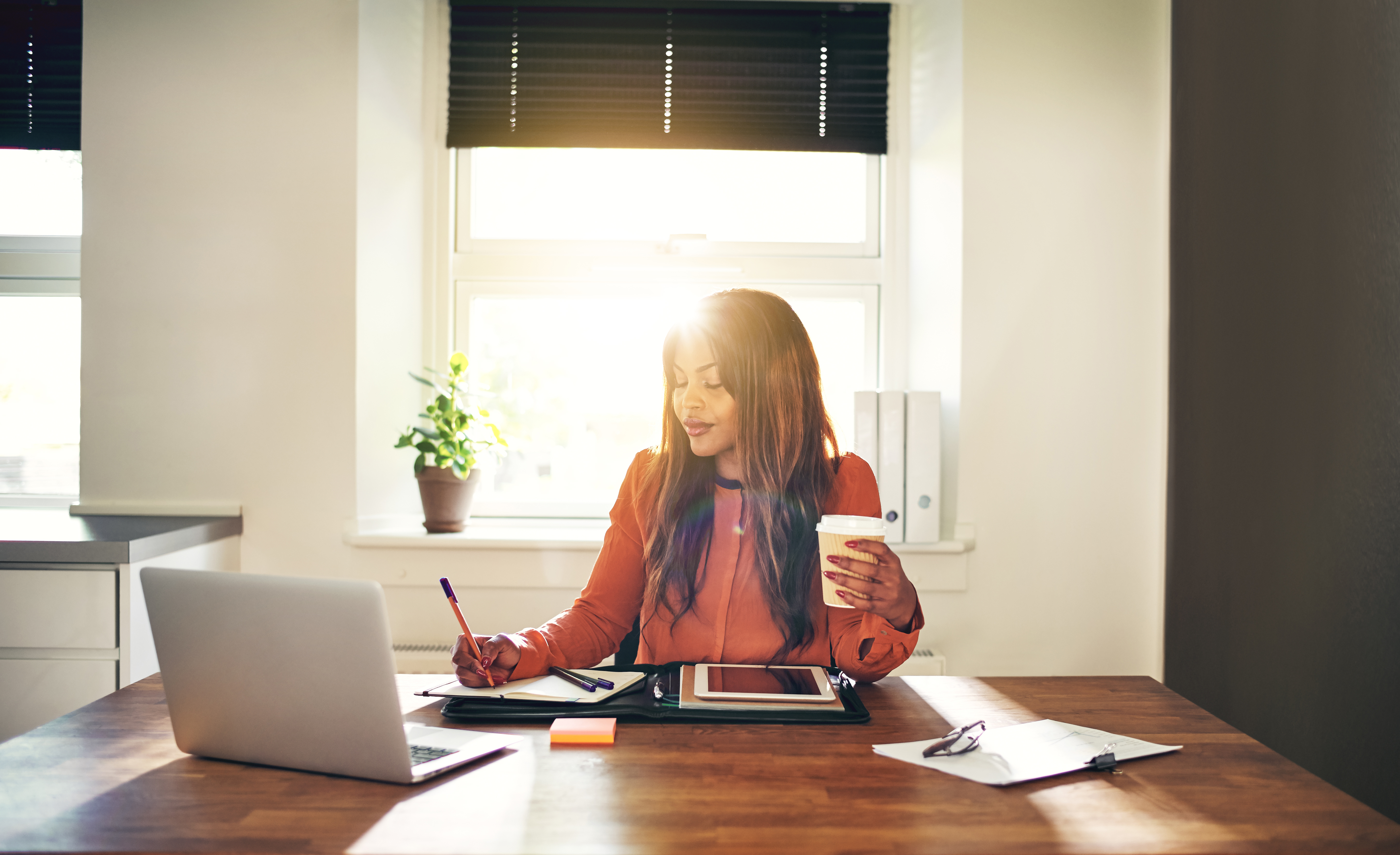 Smiling young female entrepreneur drinking coffee and working at home