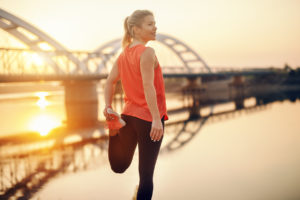 Cute Caucasian blonde woman in sportswear stretching leg by the river. It's hard to beat a person who never gives up.