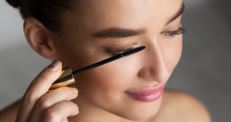 Woman Applying Black Mascara on Eyelashes with Makeup Brush, Grey Background