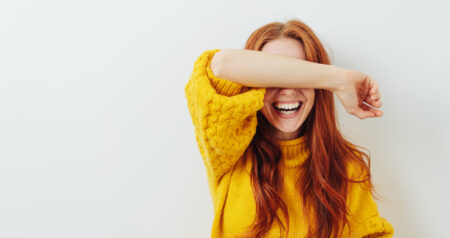 woman covering her eyes with her arm while waiting for a surprise