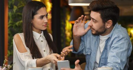 Jealous Girlfriend Showing Boyfriend Message On Phone Sitting In Cafe