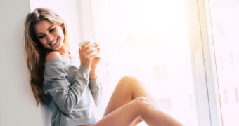 Beautiful young woman holding coffee cup and looking away with smile while sitting at windowsill at home